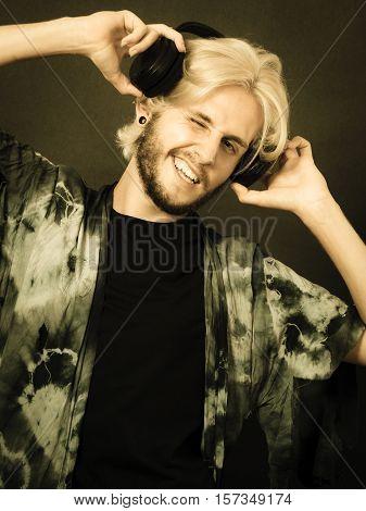 Music pasion male artist concept. Blonde man singing in studio wearing big black headphones. Indoor shot on dark grunge background sepia