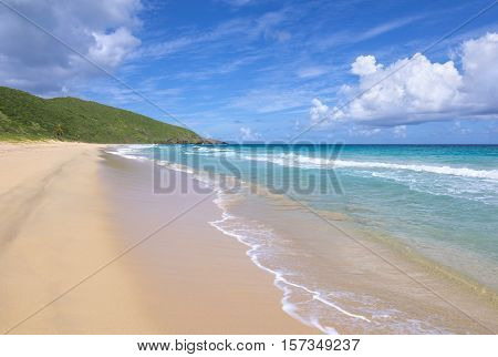 Gentle waves from crystal clear Caribbean Sea wash the sand on Resaca Beach in Isla Culebra under warm sunny sky