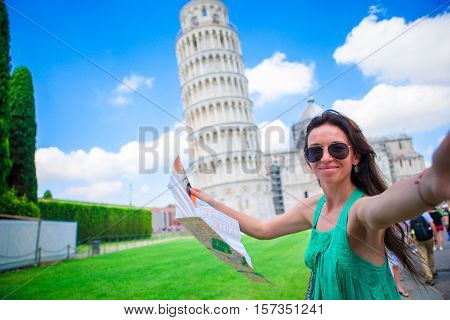 Young happy girl with toristic map on travel to Pisa. Tourist traveling visiting The Leaning Tower of Pisa, Italy