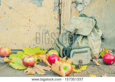 Canvas backpack and apples at the door of deserted house