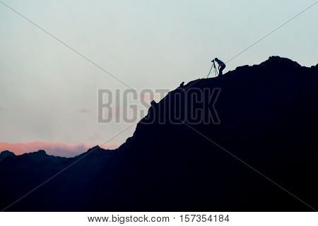 Silhouette of photographer along cliffside at sunrise