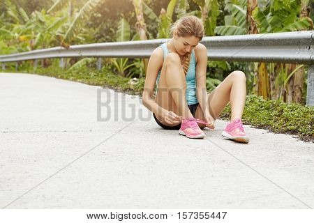 Sports And Healthy Lifestyle Concept. Young Sporty Girl Sitting On Road Lacing Her Pink Sneakers Dur