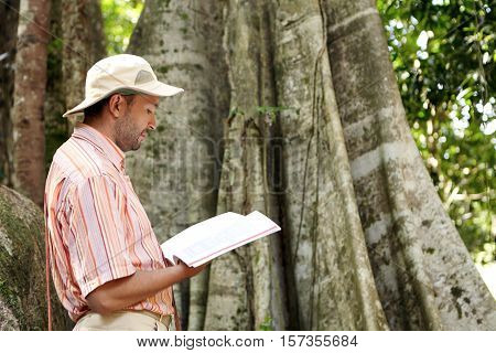 Side View Of Caucasian Male Botanist In Panama Hat And Striped Shirt Exploring Species At Field Work