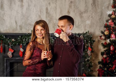 Loving couple and Christmas. Man and woman drinking from mugs Hot Christmas drink. Hot chocolate.