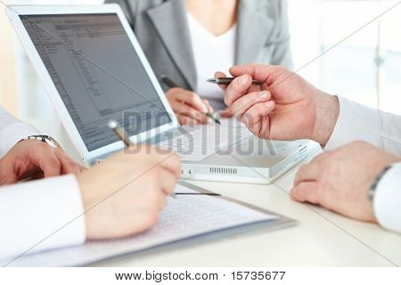 Hand of boss pointing at laptop screen at briefing