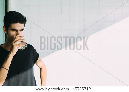 Handsome brazilian guy with earring drinking cold water from transparent glass on the balcony near window ceramic tiles behind with diagonal shadow Rio de Janeiro Brazil
