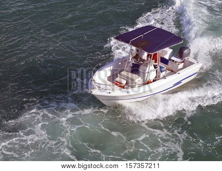 Angled overhead view of a small fishing boat powered by a single outboard engine.