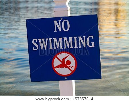 A sign showing no swimming in the water behind