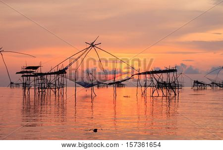 Sunrise at Pak Pra lakePattalungThailand. Silhouette of traditional fishing method using a bamboo square dip net