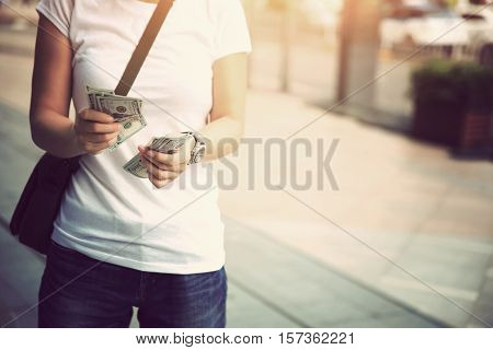 closeup of hands counting usd cash on street