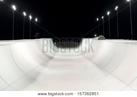Snowboarder in a snow halfpipe night lit up by lights