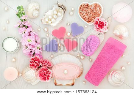 Bathroom and spa treatment with flowers, himalayan salt, moisturising cream, pumice, soaps, pink face towel, shells and pearls on distressed wood background.