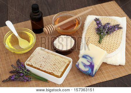 Lavender flower skin care with honey, almond oil, moisturising cream, soap, essential oil, exfoliating scrub and flannel on bamboo over oak background.