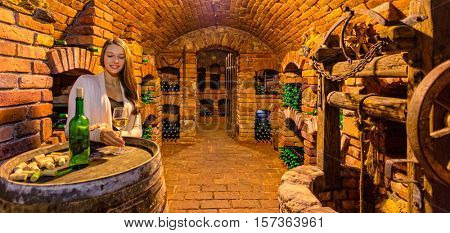Young brunette woman sommelier degusting wine in wine cellar full of bottles
