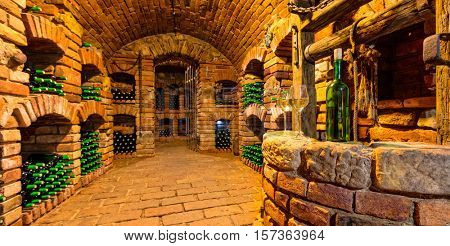 Small and old wine cellar with many full bottles. Bottle and glasses of wine on foreground