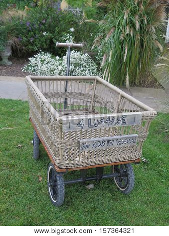Handcart with woven compartment for luggage on green grass