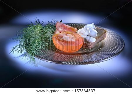 Slice of rye bread and green goods on a saucer. Light brush