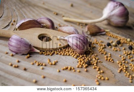 Cloves of garlic mustard seeds and spoon on wooden board. Rustic style garlic on vintage wooden background. Fresh garlic clove. Garlic bulbs.