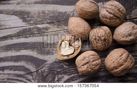 Walnuts on a grey textured wooden table. Assortment of nuts isolated on rustic old wooden background and splintered walnut with heart-shaped core. Walnuts close up.