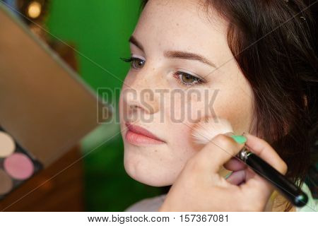 Closeup face portrait of a woman putting on makeup with brush visage