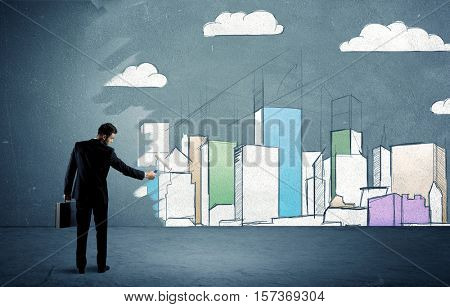 An elegant businessman standing with a paint roller transforming a blue wall into urban city landscape drawing sketch including skyscrapers and clouds concept