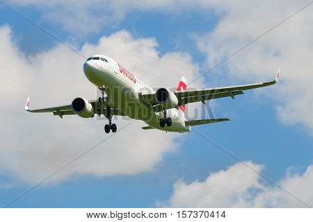 SAINT-PETERSBURG, RUSSIA - JUNE 29, 2015: Airplane Airbus A320 (HB-JLT) company Swiss International Air Lines in a cloudy sky