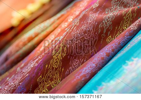 Silk fabric Thai and Asia style textured background it a Traditional silk cloth fabric crumpled in fashion store process in soft orange sun light style