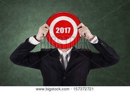 Businessman with bull's eye with number 2017 Isolated on green background