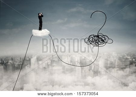 Businessman standing on the cloud and using binoculars for looking at question mark and chaos symbol on the sky