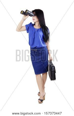 Full length of young businesswoman holding a briefcase and looking through binoculars in the studio isolated on white background