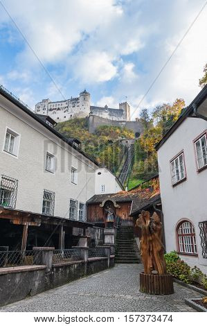 Picturesque narrow street in Salzurg Austria with funicular cable car rails leading to Hohensalzburg fortress in background