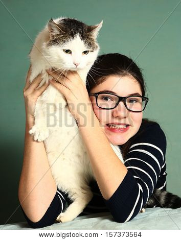 teenager girl in myopia glasses with cat close up photo