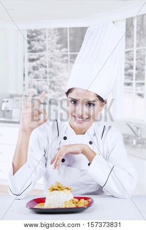 Image of cheerful female chef showing prefect sign with a delicious dish in the kitchen