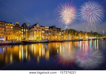 Night Amsterdam city view of Netherlands traditional houses with new year fireworks in Amsterdam Netherlands