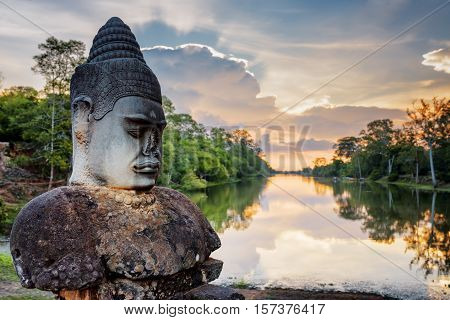 Stone Asura And Sunset Over Moat Surrounding Angkor, Cambodia