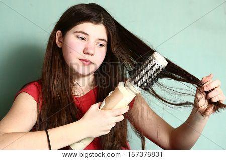 teen pretty girl with long thick dark hair use revolving straightener brush to straighten hair