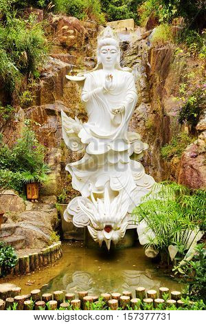 White Buddhist Statue On Background Of Small Waterfall In A Garden With Pond