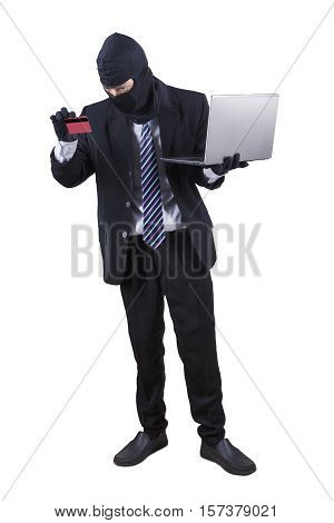 Male thief stealing money with a laptop computer and credit card isolated on white background