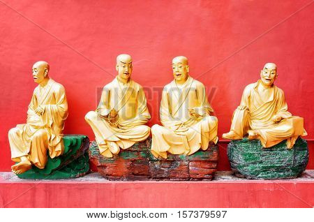 Golden Buddha Statues Outside The Temple With Red Wall In The Background