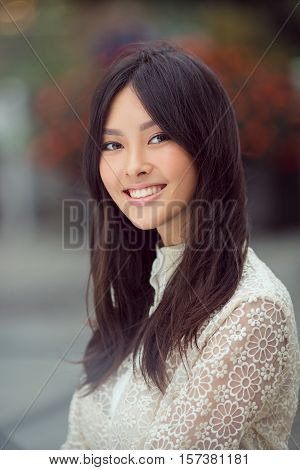 Woman smiling - portrait of happy lovely and beautiful mixed race Asian Caucasian young woman outdoor against city blurred bokeh background