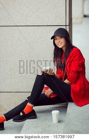 Asian beautiful woman eating a donut with coffee sitting on steps on street, fast food concept outdoors. Busy businessman loking at camera