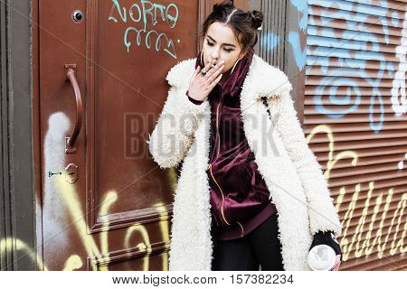 young pretty stylish teenage girl outside at city wall with graffity smoking cigarette at forbidden smoke sighn, modern fashion dressed woman