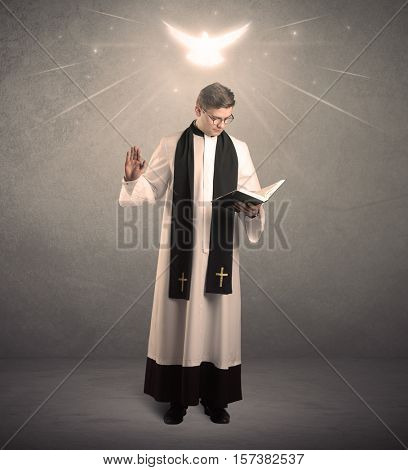 A holy priest reading a prayer from the holy bible with illustrated glowing angel above his head concept.
