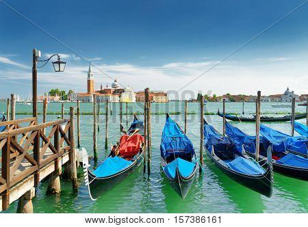 A Row Of Gondolas Parked At Pier Beside The Riva Degli Schiavoni