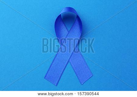 Blue ribbon on color background. Colon cancer concept