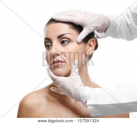 Surgeon hands examine female face for plastic operation on white background