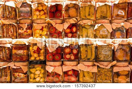 many jars with preserved italian food with vegetables and garlic and sardines in oil