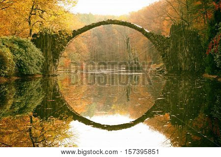 Rakotz Bridge (Rakotzbrucke Devil's Bridge) in Kromlau Saxony Germany. Colorful autumn reflection of the bridge in the water create a full circle