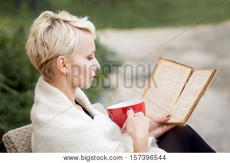 beautiful woman reading a book, holding a book in his hands.