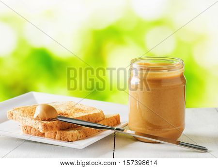 Jar Of Peanut Butter And Toasts On Nature Background